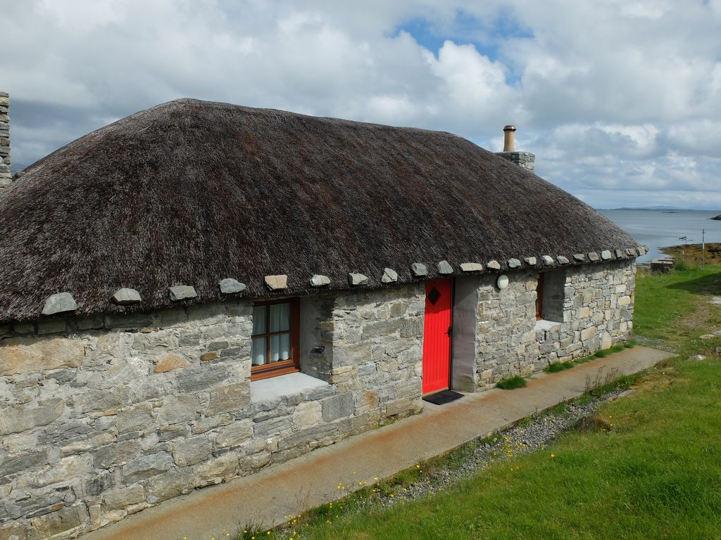 Romantic, stone built, thatched cottage, on the edge of the shore, Berneray.
